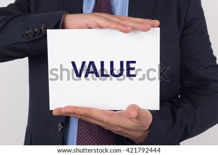 Man showing paper with VALUE text - stock photo