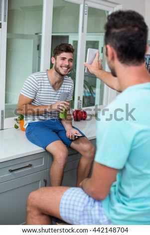 Man showing phone to smiling friend while sitting in kitchen - stock photo
