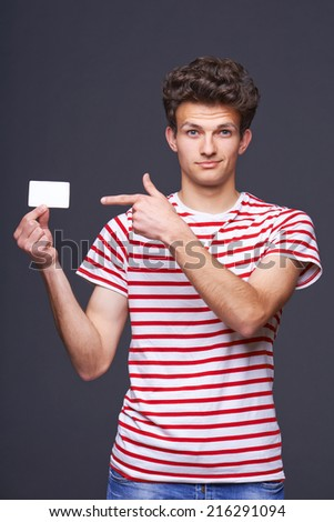 Man showing pointing at empty blank paper card sign with copy space for text, grinning with skepticism, isolated on gray background. - stock photo