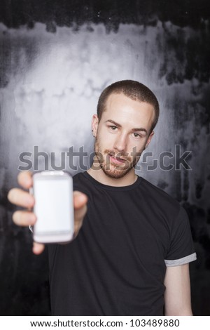 Man showing screen of smartphone, black t-shirt and background, studio shot - stock photo
