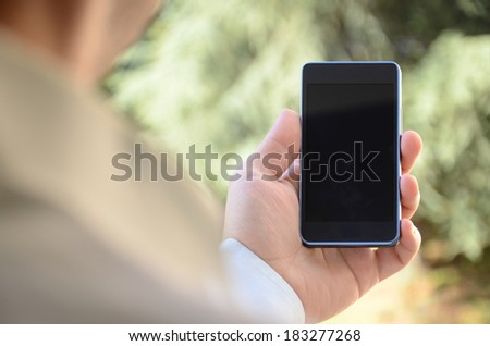 Man showing smart phone with isolated screen in hand - stock photo