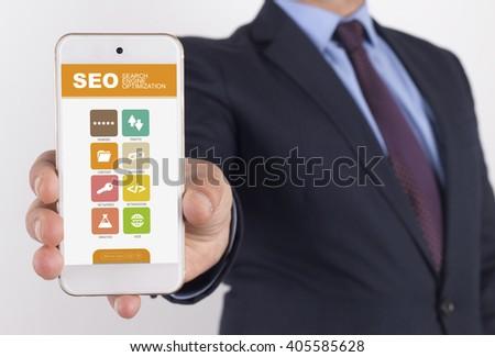 Man showing smartphone SEO on screen - stock photo