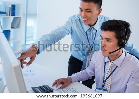 Man showing something on the screen to his colleague
