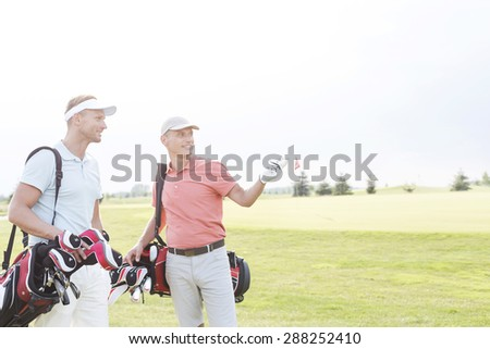 Man showing something to friend at golf course against clear sky - stock photo