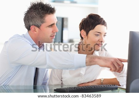 Man showing something to his coworker on a computer in an office - stock photo