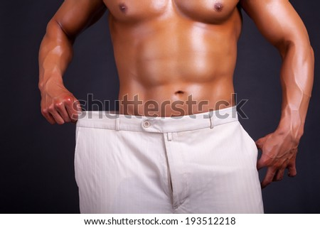 Man showing the weight he lost. Studio shooting professional lighting - stock photo