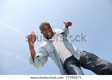 Man showing thumbs up with blue sky - stock photo