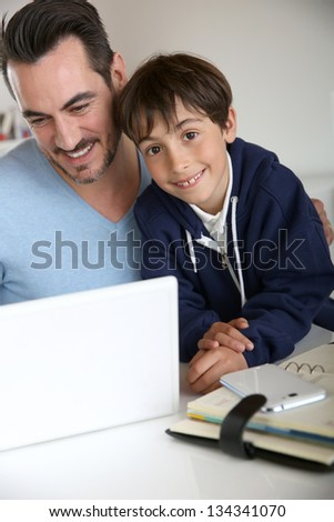 Man showing to young boy how to use laptop - stock photo