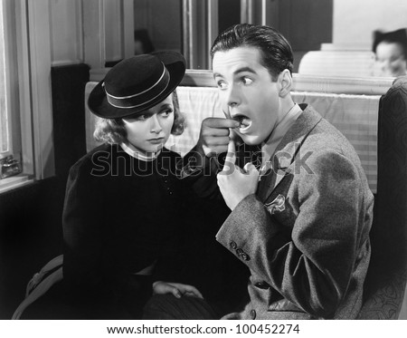 Man showing woman inside of mouth - stock photo