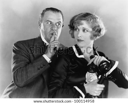Man shushing woman on telephone - stock photo
