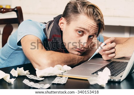 Man sick blowing his nose in his living room working notebook  - stock photo