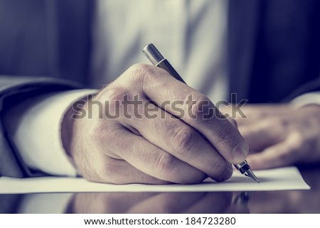 Man signing a document or writing correspondence with a close up view of his hand with the pen and sheet of notepaper on a desk top. With retro filter effect. - stock photo