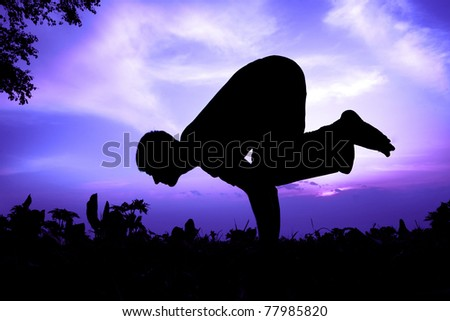 Man silhouette doing bakasana, crane pose with tree nearby outdoors at sun rise background - stock photo