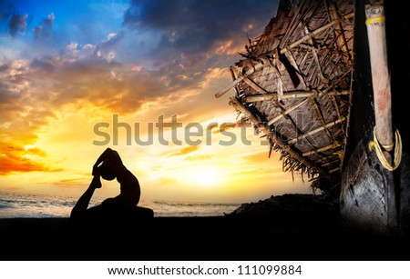 Man silhouette doing pigeon backward bending pose on the beach near the fisherman boat at sunset background in India - stock photo