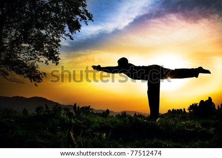 Man silhouette doing virabhadrasana III warrior pose with tree nearby outdoors at sunset background - stock photo