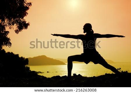 Man silhouette doing virabhadrasana warrior II pose near the ocean in Gokarna, Karnataka, India - stock photo