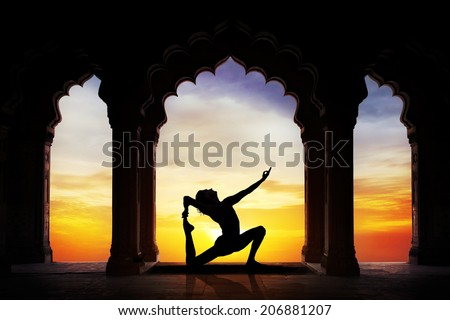 Man silhouette doing yoga advance pose in old temple at orange sunset sky background