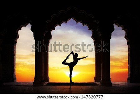 Man silhouette doing yoga in old temple at orange sunset sky background