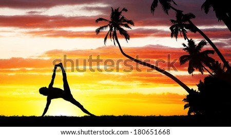 Man silhouette doing Yoga near the palm trees at sunset - stock photo
