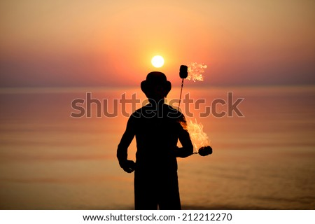 Man silhouette in bowler spinning fire poi on background of beautiful sunset  - stock photo