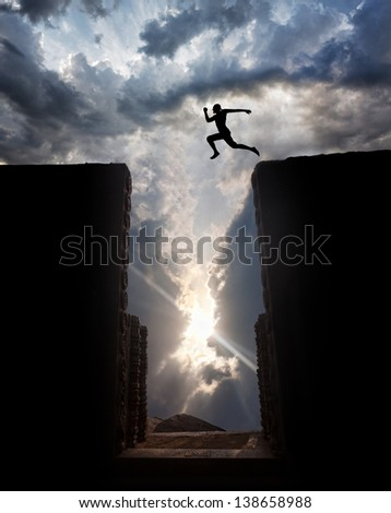 Man Silhouette jumping over the abyss at sunset cloudy sky background - stock photo