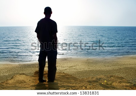 man silhouette looking at the sea - stock photo