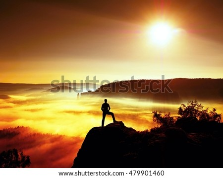 Man silhouette on the sharp peak. Satisfy hiker enjoy view. Tall man on the peak of cliff watching down to landscape. Vivid and strong vignetting effect.