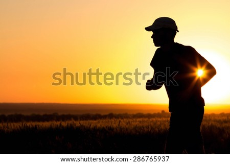 Man silhouette running in the field