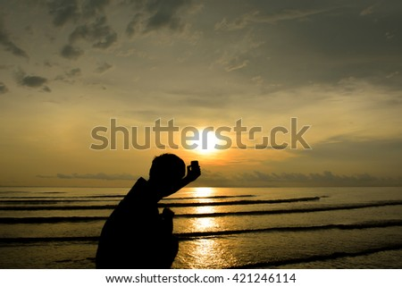 Man silhouette selfie. Background sunset on the sea