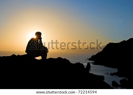 man silhouette sitting on a marine cape at the evening
