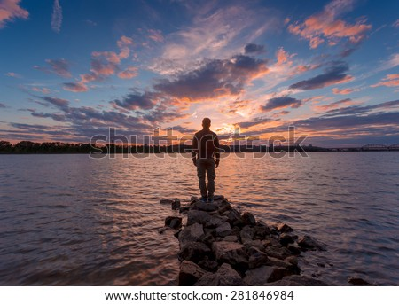 Man silhouette, standing on river stones gangway and contemplating a beautiful sunset. - stock photo