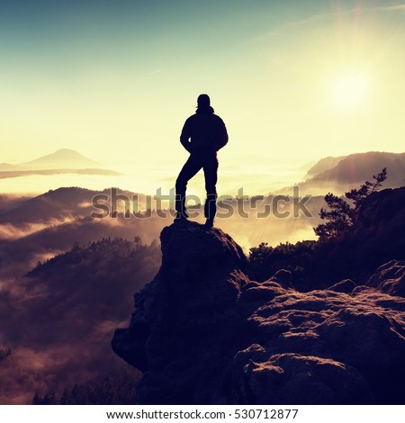 Man silhouette stay on sharp rock peak. Satisfy hiker enjoy view. Tall man on rocky cliff watching down to landscape. Vivid and strong vignetting effect.