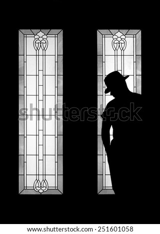 Man silhouette wearing fashionable gangster mafia hat in decorative door window looking mysterious solitary meditative reflective lonely thoughtful dangerous serious as an outcast outsider secret - stock photo