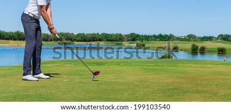 Man simulates play golf. With the stick on the green field. - stock photo