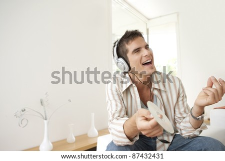 Man singing to music at home, using headphones - stock photo