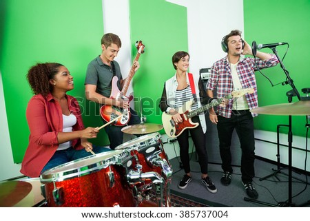 Man Singing While Colleagues Playing Musical Instrument - stock photo