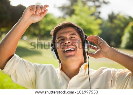Man singing with his arms raised as he uses headphones to listen to music in a park - stock photo