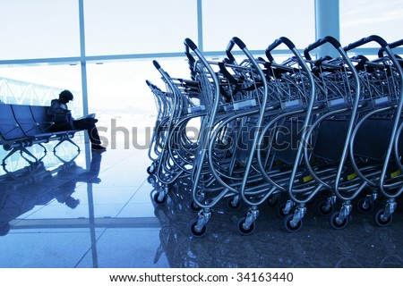 Man sit in a airport with trolleys - stock photo