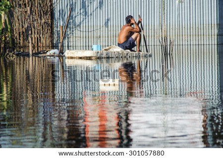 Man sit safety on a flooded section of road in Bangkok - stock photo