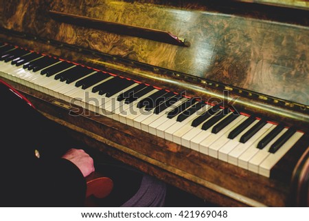 Man sits at an old vintage piano - stock photo