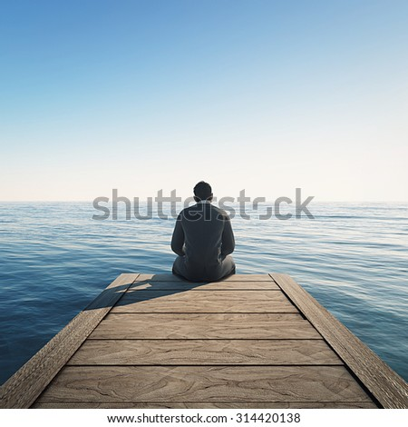 Man sits at wharf and looking at the sea. - stock photo