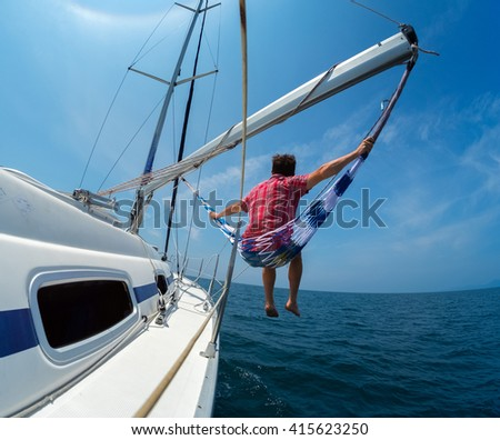 Man sits in the hammock set on the sail boat - stock photo