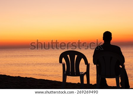 Man sits on chair alone in sunset - stock photo