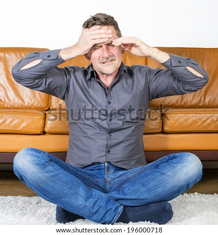 man sits on floor in living room with a headache - stock photo