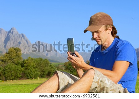 Man sits on grass and looks into his smartphone/computer/gps - and misty mountains are background. Shot in Stellenbosch, South Africa.