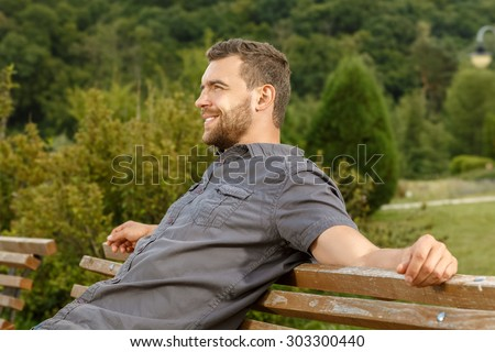 Man sits on the bench and relax in public park - stock photo