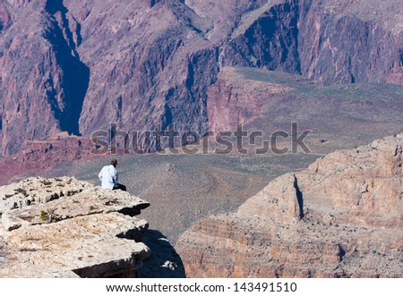 Man sits on the edge of the Grand Canyon - stock photo