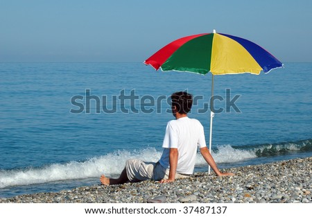 Man sits under umbrella on seaside