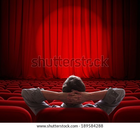 man sitting alone in  empty theater or cinema hall - stock photo