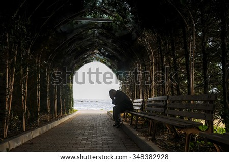 man sitting alone on the bench in the tunnel - stock photo
